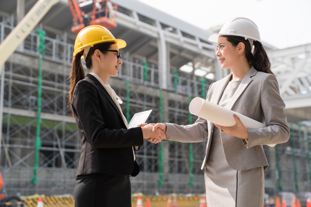 Foto für Two female architect shaking hands after they finish their building project with a satisfying smile. - Lizenzfreies Bild