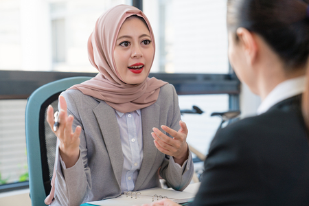 Photo for Muslim businesswoman explains talk her opinion to Asian office lady. They are discussing their future. - Royalty Free Image