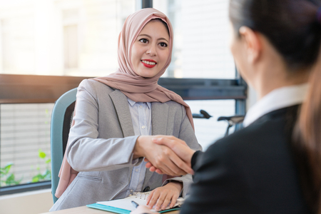 Photo pour Muslim foreign manager deal with office lady. They have a good partnership. They are shaking hands in the office. - image libre de droit