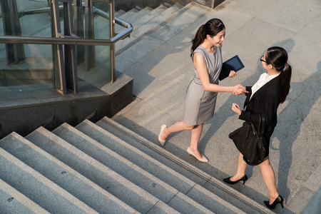 Photo pour Two business Asian lady meet each other before they start their interview . Supervisor wearing dress and employee in a black suit.They will start a good cooperation with each other. They shake their hands down the stairs. - image libre de droit