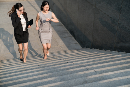 Foto de Moder Asian business lady have a rush time to attend the show meeting. They nervously communicate with their co-workers. They are running on the stairs. Afraid to be late. - Imagen libre de derechos