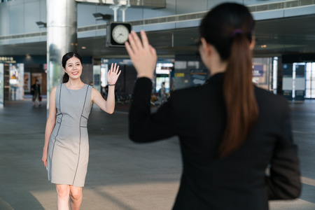 Photo pour Two Asian office lady meet in the modern company and wave their hands to greet each other. - image libre de droit