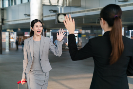 Foto per The Asian assistant shows up in the station to pick up her boss who is carrying a suitcase. They are going to attend a meeting. They say hello and wave their hands to each other. - Immagine Royalty Free