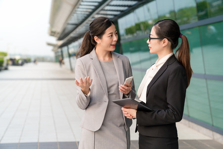 Photo for Asian supervisor talking excitingly to the employee outside a modern company. - Royalty Free Image