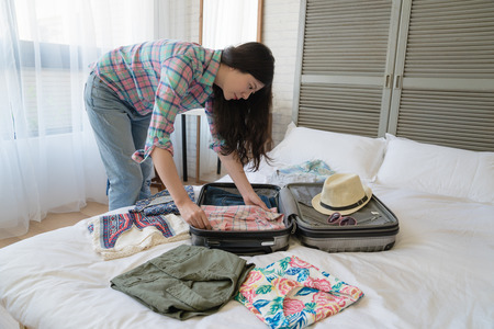 Photo for Side view of the Asian female tourist preparing her suitcase. She folded every clothes nice and neat. - Royalty Free Image