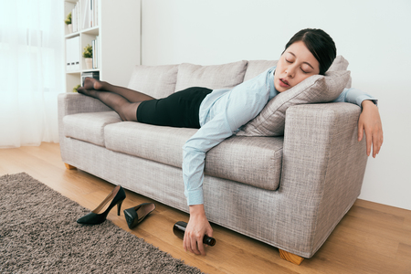 Foto de she is drunk and fell asleep on the sofa in the living room at home - Imagen libre de derechos