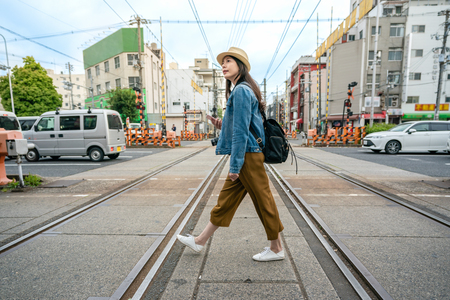 Photo for relaxed travel woman walking across the railroad holding her phone in osaka city in japan. - Royalty Free Image
