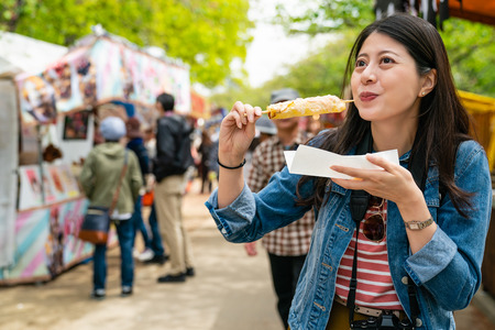 Photo pour happy cute asian gilr eating japanese street food and looking enjoyable in a traditional small fair. - image libre de droit