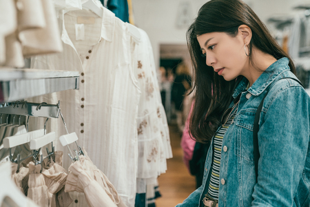 Photo pour pretty young asian woman browsing and choosing clothes in a ready to wear store. - image libre de droit