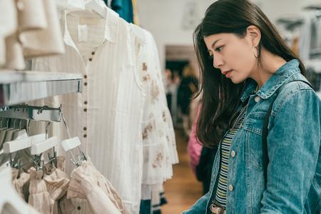 Foto de pretty young asian woman browsing and choosing clothes in a ready to wear store. - Imagen libre de derechos