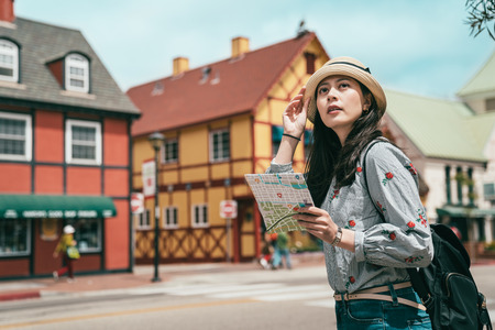 Photo pour a pretty asina woman having sightseeing with a map while stepping in a lovely and beautiful old town. - image libre de droit