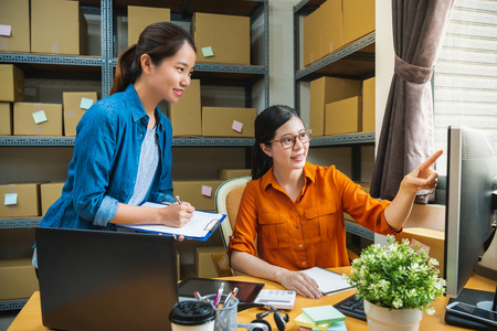 Photo for manager in the delivery company is teaching the new employee to check the list, and the new staff is making note - Royalty Free Image
