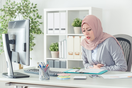 Photo for muslim kerchiefed businesswoman having stomachache and carrying abdomen in breast. Office lady feels uncomfortable at work. woman in office suit is sick. - Royalty Free Image
