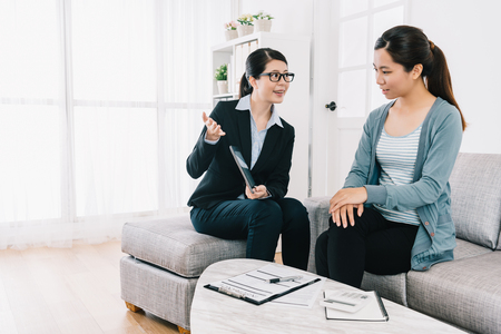 Photo pour professional female insurance agent giving customer her best advice of the insurance plan. lawyer helping housewife solving problem at home. bright modern house lifestyle. - image libre de droit