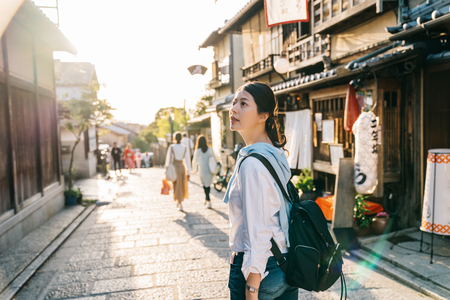 Foto de traveler stopped on the street and looking at the Japanese traditional building. Japan travel tourist woman on vacation in Kyoto shopping in alley. cheerfully visit kyoto. - Imagen libre de derechos