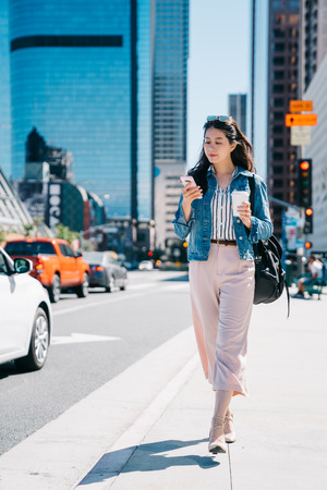 Photo for office lady holding coffee and cellphone, walking on the street to work. fresh graduate started working in the city center in LA. Young female worker lifestyle. - Royalty Free Image