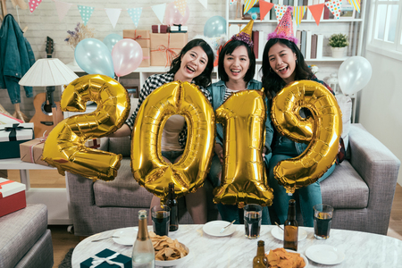 Photo for attractive girls celebrating new year eve at home. young friends carrying gold 2019 number balloons cheerfully having fun in house party. asian women indoor lifestyle concept. - Royalty Free Image