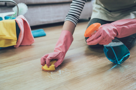 Foto de people doing housework and housekeeping concept. close up of woman in rubber gloves with scouring pad cleaning wooden floor at home. lady spraying cleaner on the ground in the living room. - Imagen libre de derechos
