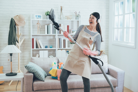 Foto de cheerful asian wife wearing earphones playing vacuum cleaner as a guitar enjoy music dancing while doing housework in the living room. young housewife joyfully doing house chores at home. - Imagen libre de derechos