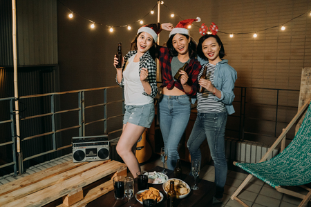 Photo pour Roof party with group of best friends. three young cheerful people dancing and drinking beer on rooftop of the building. happy carefree asian women enjoy music on balcony at night. - image libre de droit