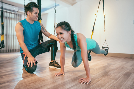 Photo pour asian woman performing total body resistance exercise training in gym with personal coach. Sporty girl doing kicking legs exercise with elastic rope. sportswoman works out at health club. - image libre de droit