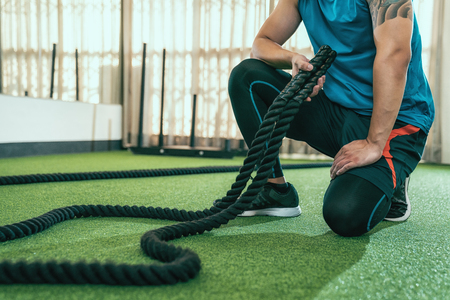 Photo pour unrecognized man with tattoo kneeling down resting after training with battle rope. asian sporty male trainer tidy up the classroom in gym after a battling ropes lesson. athlete stronger arms muscle. - image libre de droit