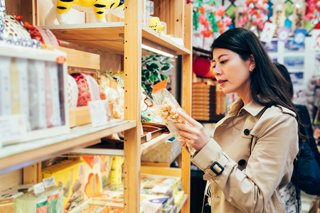 Foto de young japanese mom choosing snack for kids in local specialty shop in dotonbori osaka japan. asian mother buying food cookies for family after work in the vendor. beautiful lady reading the mark. - Imagen libre de derechos