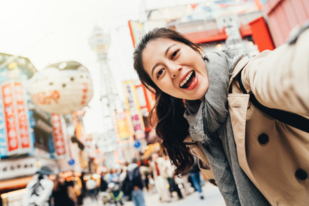 Foto de young female traveler cheerfully taking selfie on busy street in tsutenkaku osaka japan. girl smiling at the camera self portrait with peffer fish balloon floating on the sky in sunshine. - Imagen libre de derechos