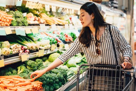 Photo pour japanese woman in supermarket pushing shopping cart walking by the vegetables and fruits area. pretty asian lady picking up carrots beside broccoli purchase food health care. wife prepare for dinner - image libre de droit