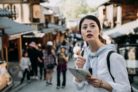 Foto de asian woman tourist holding paper map pointing to direction standing in Sannen Zaka street kyoto japan. girl backpacker self guided trip in summer vacation travelers visit famous attraction old town. - Imagen libre de derechos