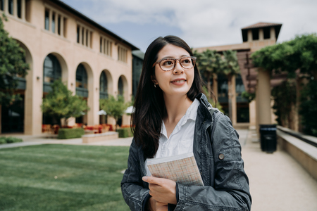 Foto de Attractive smiling charming asian young girl student with school book relaxing walking in university outdoor. - Imagen libre de derechos