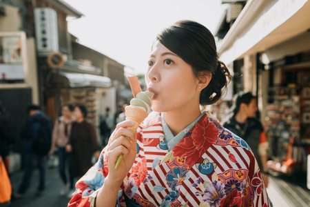 Foto de japanese young teenage girl in flower kimono dress join having fun in summer festival join temple fair. happy woman in traditional cloth eating matcha ice cream kyoto japan in hot teeming street - Imagen libre de derechos