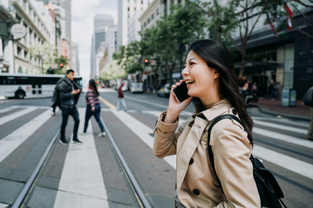 Photo for happy asian woman worker talking on cellphone having fun chatting with friends laughing. young office lady crossing zebra road light railway in city san francisco. busy business area public commute - Royalty Free Image