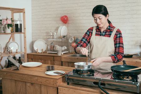 Photo pour Cooking happy woman wear pinafore in wooden kitchen with pot stir melting chocolate to make sweet dessert for valentine day. young beautiful girlfriend handmade cocoa using spoon cooking on stove. - image libre de droit