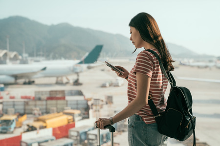 Foto de side view of beautiful travel lady with backpack and luggage suitcase walking to departure lounge in hall. tourist woman standing near window using cellphone chatting online airplanes on runway. - Imagen libre de derechos