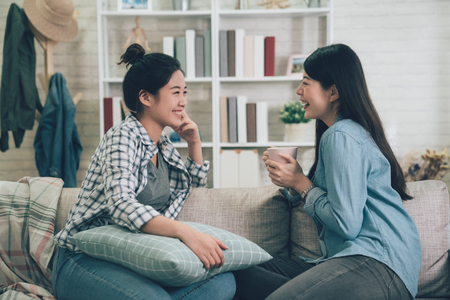 Foto de Two asian casual women relaxing on sofa with hot drink. - Imagen libre de derechos