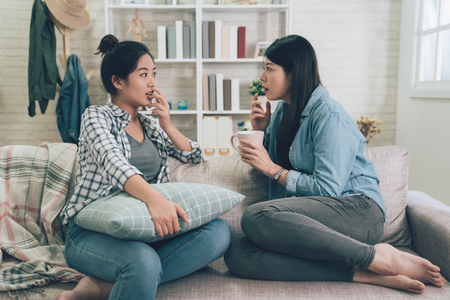 Foto de Two asian girls gossiping at home. - Imagen libre de derechos