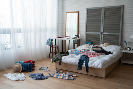 Foto de modern bright bedroom with messy clothes scatter on white bed and floor. - Imagen libre de derechos