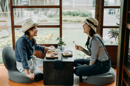 Foto per two girlfriends laughing with jokes drinking matcha  having tea ceremony experience. - Immagine Royalty Free