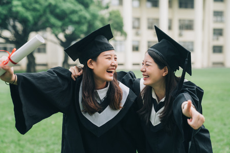 Photo pour cheerful ladies students hugging shoulders arms with thumb up finger and looking each other smiling - image libre de droit