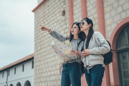 Photo pour Young asian woman missed the road. two girl backpackers trying to find right way with paper map. - image libre de droit