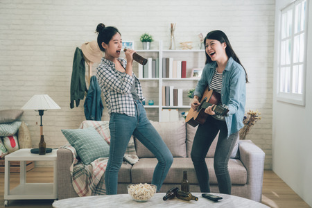 Photo pour Young happy girl best friends having party together by playing guitar and another singing by holding beer bottle as microphone. - image libre de droit