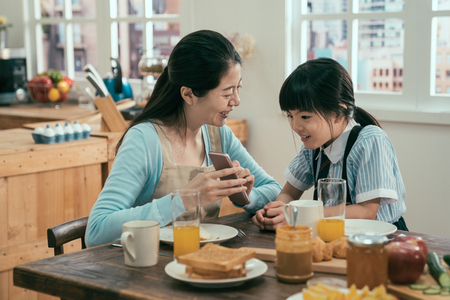 Foto de Funny mom and lovely child are having fun with phone. young asian housewife in apron and cute daughter in uniform sitting at morning kitchen table with tasty healthy meal breakfast. kid interested. - Imagen libre de derechos