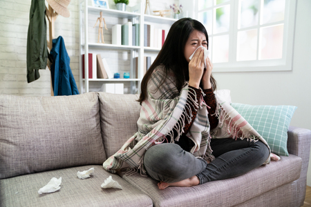 Photo for asian illness lady with seasonal infections flu and runny nose using tissue on sofa at home. - Royalty Free Image