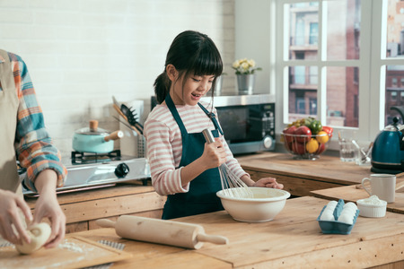 Foto per unrecognized mom hands beside in wooden kitchen at home kneading dough on plate. cute happy daughter kid holding whisk mixing flour and eggs for baking bread. child making surprised for mothers day. - Immagine Royalty Free