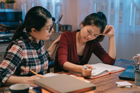 Foto de smart woman friend in glasses comforting to sad student with failed exam sitting in night home kitchen prepared for test again. two young girls studying in late midnight. lady consoling crying sister - Imagen libre de derechos
