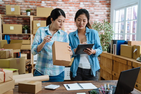 Foto de Young women teamwork partners packing order into box together using touchpad to do delivery to client. two asian female colleagues with tablet checking goods number and prepared cardboards in office. - Imagen libre de derechos