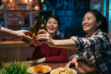 Photo for Group of happy friends drinking and toasting beer at brewery bar at late night. - Royalty Free Image