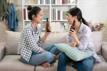 Foto de Group of young asian girl friends sitting on sofa and discussing something together with beer at home. - Imagen libre de derechos