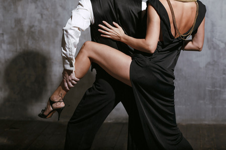 Foto de Young pretty woman in black dress and man dance tango - Imagen libre de derechos